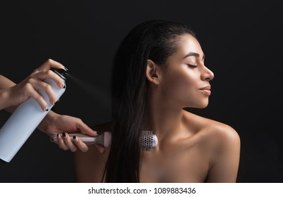 Profile of calm lady making hairdo. Hairdresser using hairspray and comb. Isolated on background