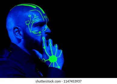 A profile of a caucasian male model with green blacklight paint. Paint resembles a circuit board. Dark suit with green accents