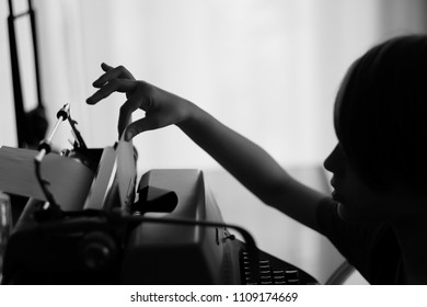 Profile of a child pulling a sheet of paper from an old mechanical typewriter