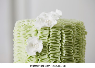 Profile Close Up of Exquisite Cake Decorated with Green Fondant Ruffles and White Sugar Flowers