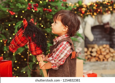 Profile close up warm portrait of small boy with dark messy hair, sweet beautiful face, looking up, checked collar shirt, suede vest, holding hobbyhorse on stick, blurred background, Christmas tree