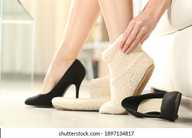Profile close up of woman taking off high heels and putting slippers sitting on a couch in the living room at home