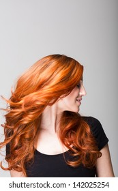 Profile of a cool redhead woman flicking her gorgeous long wavy hair so that it is flying loose around her face