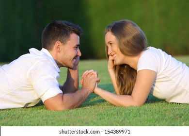 Profile of a couple in love flirting and looking each other lying on the grass with a green background