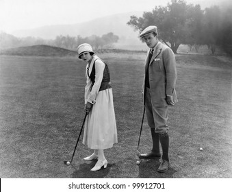 Profile of a couple playing golf in a golf course