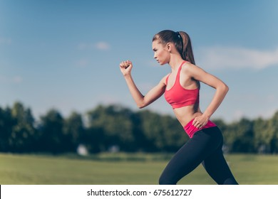 Profile cropped photo of young lady athlete, running outdoors, training for marathon run, in fasionable sports outfit, so focused, fit and fast!