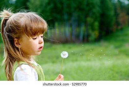 Profile of cute girl with white dandelion looking at it in the park