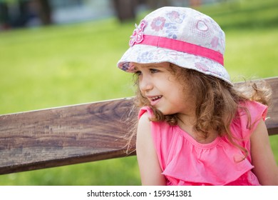 Profile of cute little girl in a park. Close-up of beautiful child, outside