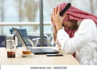 Profile of a desperate and alone arab saudi man with a laptop online in a coffee shop with a window in the background. Bankruptcy concept
