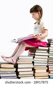 Profile of diligent pupil sitting on pile of books and reading one of them