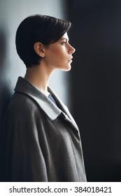 Profile dramatic portrait of beautiful girl near grey wall