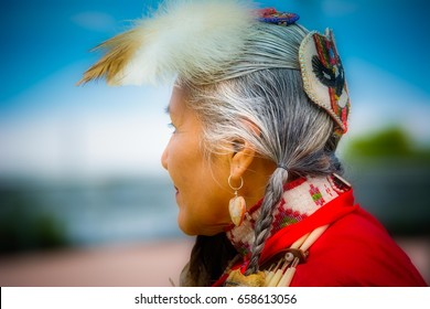 Profile of elegant Lady Pow Wow dancer at an event in Mesa, Arizona on 4.1.2017, Native American woman, Orton effect on feather, stylized portrait