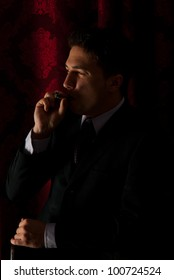 Profile of elegant man smoking in night and looking to the light