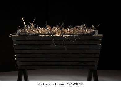 Profile of empty wooden manger filled with hay.