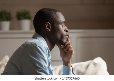 Profile face sad african guy in tension touch chin lost on thoughts thinking sit on couch in living room alone, try to make difficult decision, going through divorce or break up personal life problems