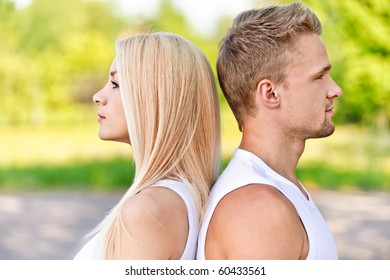 Profile face of young smiling couple against summer park.