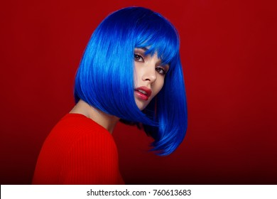 Profile of fashionable, beautiful model, dressed in red, with short blue wig and amazing make up, posing in studio on dark red background. Horizontal view.
