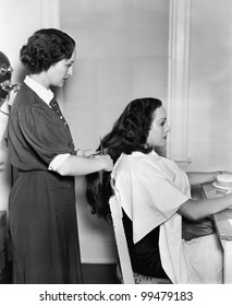 Profile of a female hairdresser cutting a young woman's hair