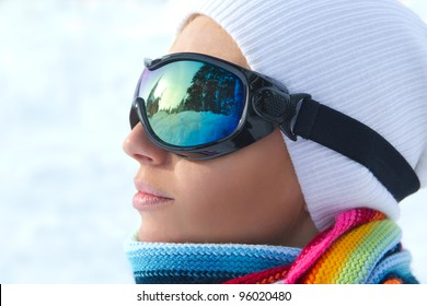 Profile of female skier wearing ski glasses in the mountains