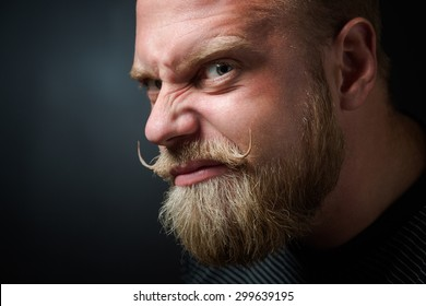 Profile of frightening bearded man on black. Man with serious glance looking with wickedness and narrowing his eyes.