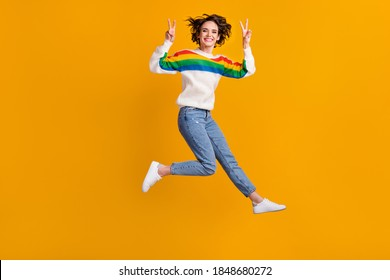 Profile full size photo of cheerful funny young woman jump show v-sign wear sweater jeans footwear isolated on yellow background