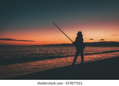 Profile of a girl is fishing on the beach near the sea in the night.