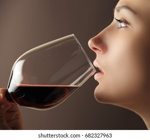 Profile of girl with smooth clean skin holding wine glass with red wine. Portrait of girl with red wine close-up.