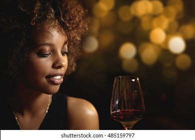 Profile of good-looking dark-skinned girl with make-up and Afro hairstyle, holding glass of wine, sitting at bar against blurred lights background with copy space for your text or advertising content