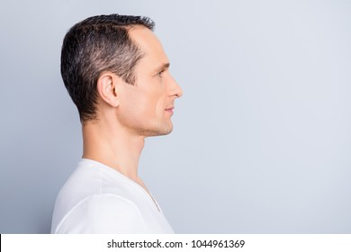 Profile, half face portrait with copy space of trendy, attractive, stylish, man looking at empty place for advertisement, product, having perfect ideal oiled, dry skin, isolated on grey background