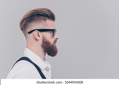 Profile half-faced side view portrait of serious confident concentrated attractive manager with blonde hair wearing rimmed glasses white shirt black suspenders isolated on gray background empty blank