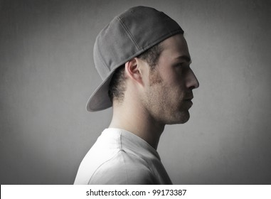 Profile of a handsome young man wearing a peaked cap