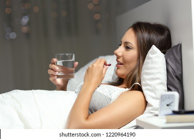 Profile of a happy girl taking a pill before sleep on a bed in the night at home