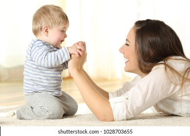 Profile of a happy mother and her kid son holding hands lying on the floor at home