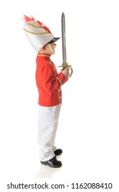 The profile of a happy preschool Christmas soldier standing erect with his sword pointing upward.  On a white background.