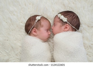 Profile headshot of two fraternal twin newborn baby girls sleeping and swaddled in white.