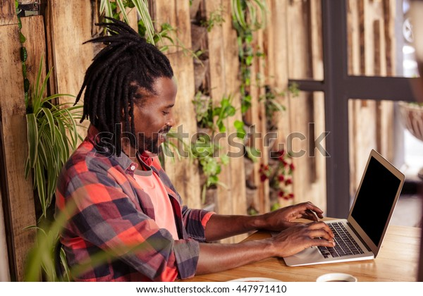 Profile of hipster man using laptop at cafe
