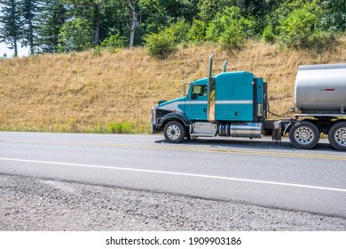 Profile of industrial big rig diesel semi truck tractor with vertical pipes and extended cab compartment transporting fuel in stainless steel tank semi trailer running on the road with hill and trees