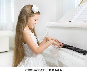 Profile of little girl in white dress playing piano. Concept of music study and art
