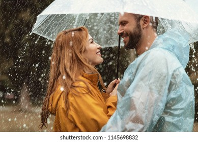 Profile of loving couple spending date outside. They are standing under umbrella and looking at each other with care and smile