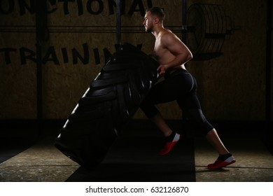 Profile of man doing cross training. Sportsman pulling tire with knee. Full body of man doing exercises with tires. Indoors, interior of the gym