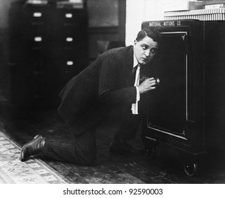 Profile of a man opening the door of a safe