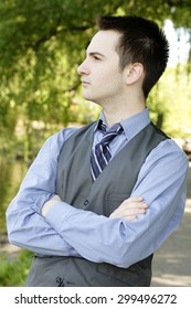 Profile of man standing with arms folded.