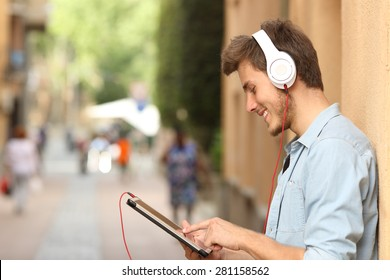 Profile of a man using a tablet with headphones on the street and touching the screen with the finger