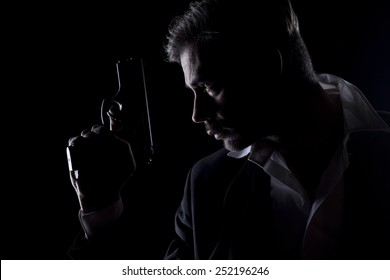 Profile of men's silhouette in the dark with a gun in his hand