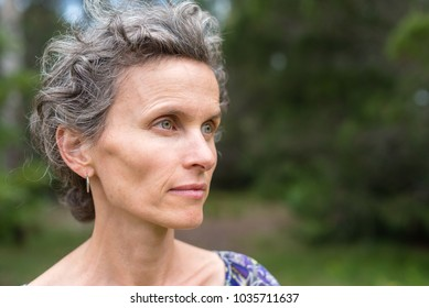 Profile of middle aged woman with grey hair against forest background (selective focus)