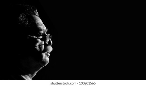 profile middle-aged man with glasses  on black background