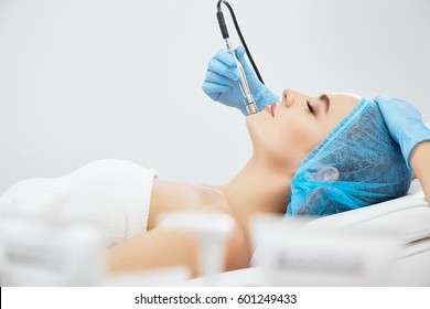 Profile of model in blue cap lying on couch in cosmetological clinic with closed eyes, cosmetology. Doctor's hands in blue gloves doing procedure of microdermabrasia on woman's face