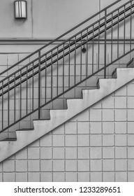 Profile in Monochrome of a Stairway and Light with Iron Railing and Cube Block Construction.