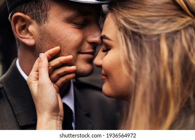profile of newlyweds. the groom in military uniform closed his eyes and the bride touches his face with his hand. close up.