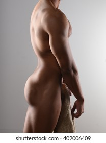 Profile of a nude male bodybuilder holding a towel
